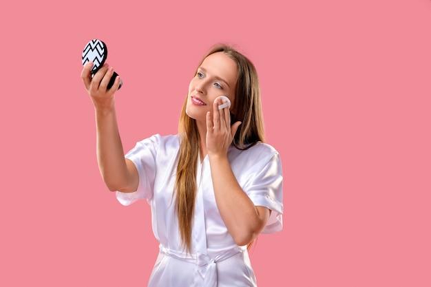 Bella donna su sfondo rosa, applicare le fondamenta sul viso