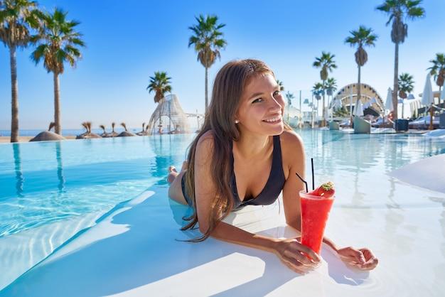 Bella donna sulla piscina a sfioro con cocktail