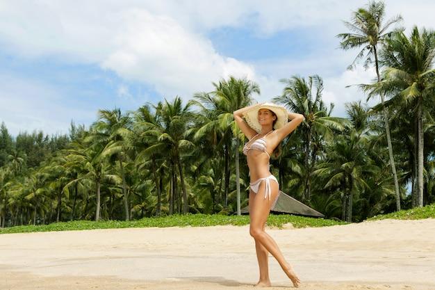 Bella donna sulla spiaggia con palme