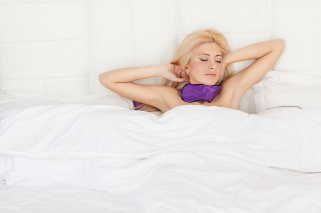 Bella donna svegliarsi nel letto.
