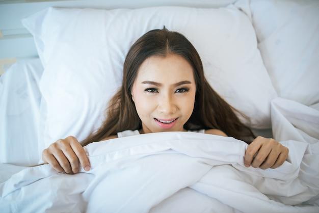 Bella donna svegliarsi nel suo letto, pigro al mattino