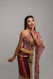 Bella donna tailandese che porta vestito tailandese e che esamina la cima