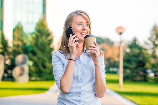 Bella donna texting su un telefono astuto in un parco con uno sfondo verde