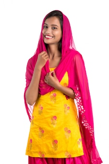 Bella donna tradizionale indiana che posa sul bianco.