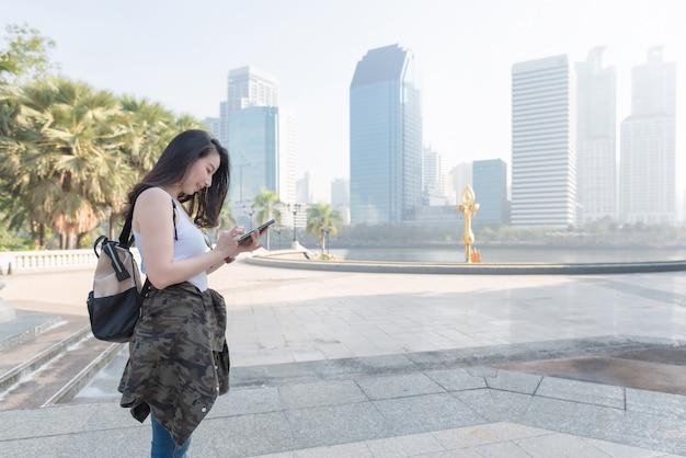 Bella donna turistica asiatica che esamina telefono cellulare per la ricerca della posizione del punto di riferimento.