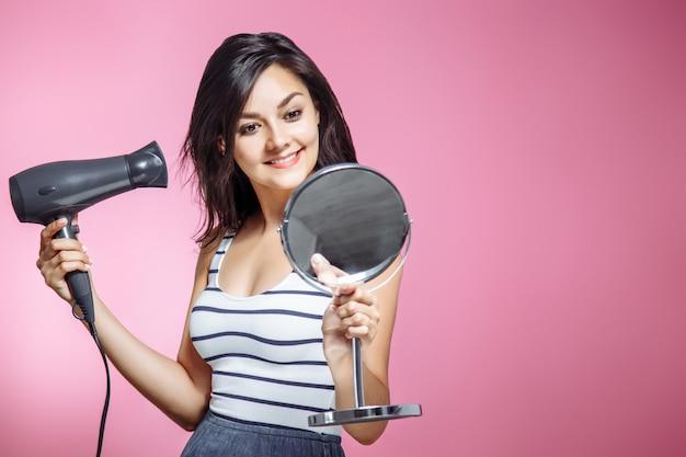 Bella donna usando un fon e sorridente mentre guardando lo specchio su uno sfondo rosa.