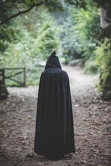 Bella donna vampiro scuro con mantello nero e cappuccio