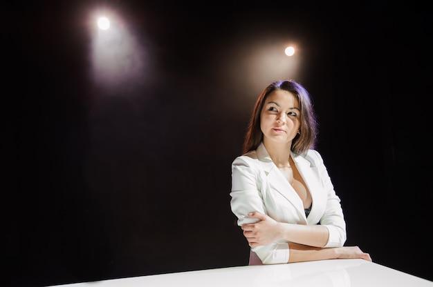 Bella donna vicino al piano bianco sulla scena