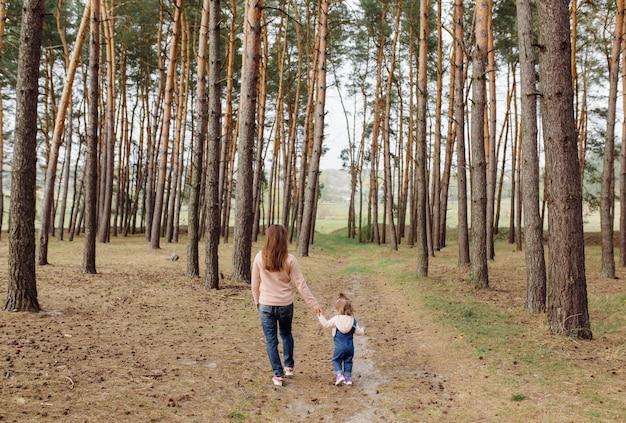Bella e felice madre e figlia che si divertono nella foresta