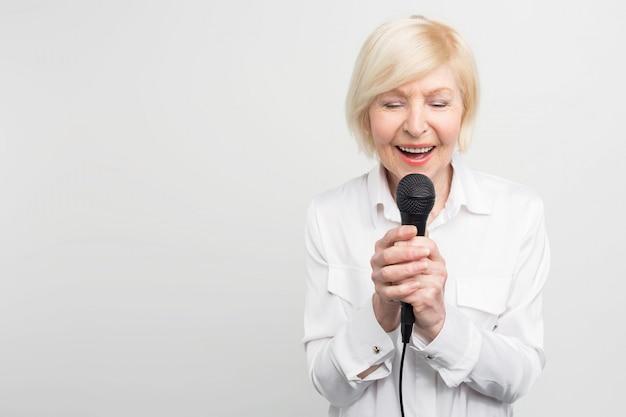 Bella e tenera foto di una donna matura meravigliosa che canta una canzone con gli occhi chiusi usando un microfono.