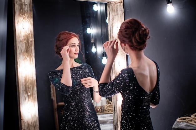 Bella ed elegante donna in abito da sera nero si trova accanto allo specchio scuro alto