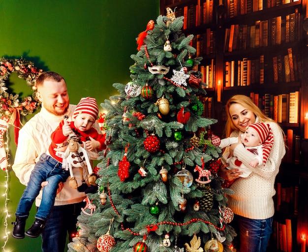 Bella famiglia con bambini in maglioni caldi si pone davanti a un muro verde e un ricco albero di natale
