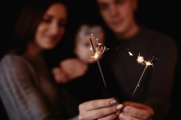 Bella famiglia con bambino festeggia il natale e tiene le stelle filanti