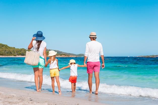Bella famiglia di quattro felice sulla spiaggia bianca