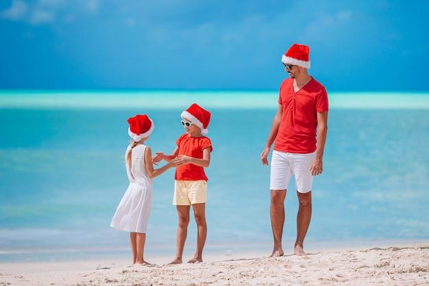 Bella famiglia felice in cappelli rossi di santa su una spiaggia tropicale che celebra il natale
