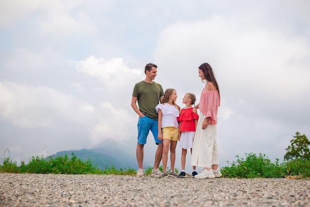 Bella famiglia felice in montagna sullo sfondo della nebbia