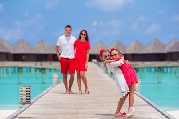 Bella famiglia felice sul molo di legno durante le vacanze estive al resort di lusso