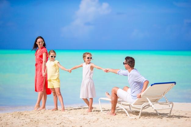 Bella famiglia felice sulla spiaggia bianca divertendosi