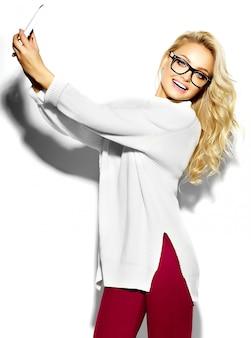 Bella felice dolce carina donna bionda sorridente in abiti casual caldo maglione bianco hipster, in bicchieri prendendo selfie