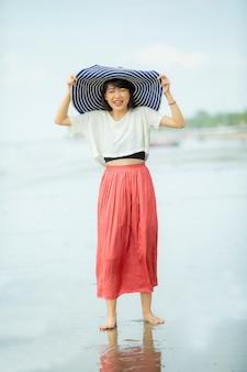 Bella felicità asiatica della giovane donna sulla spiaggia del mare di vacanza