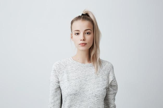 Bella femmina attraente con la coda di cavallo bionda, sentendosi autoassicurante mentre posa contro la parete in bianco.