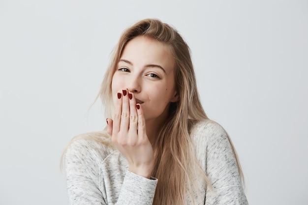 Bella femmina bionda dall'aspetto piacevole con il manicure rosso soffia bacio