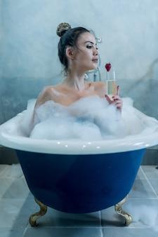Bella femmina con champagne fare il bagno