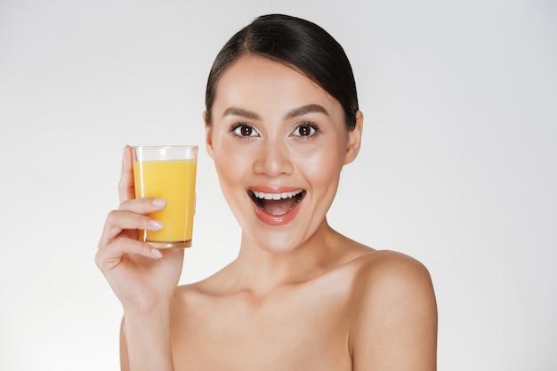 Bella foto di donna seminuda con i capelli scuri in panino e ampio sorriso che beve il succo d'arancia da un vetro trasparente, isolato su un muro bianco