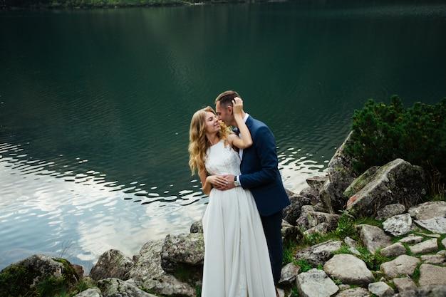 Bella foto di nozze sul lago di montagna. felice coppia asiatica in amore