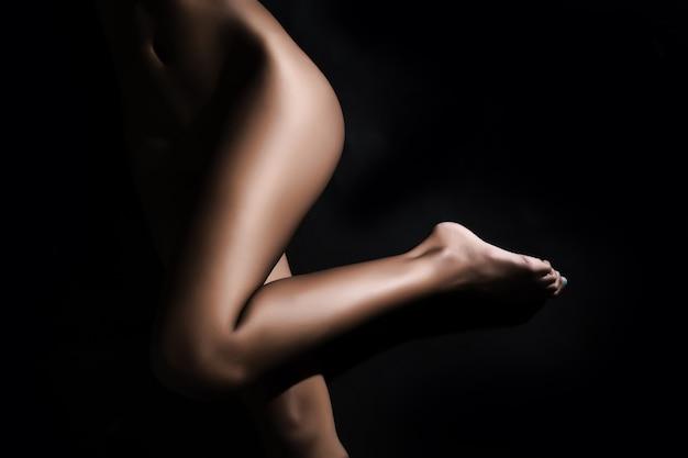 Bella gamba di un corpo nudo giovane donna sdraiata di fronte a sfondo nero