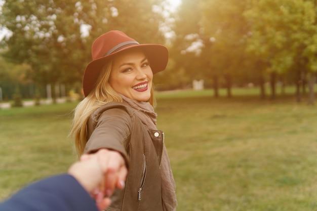 Bella giovane bionda in cappello bordeaux sorridente esaminando la fotocamera e tenendo la mano di un uomo non identificato e camminando con lui sul soleggiato parco d'autunno