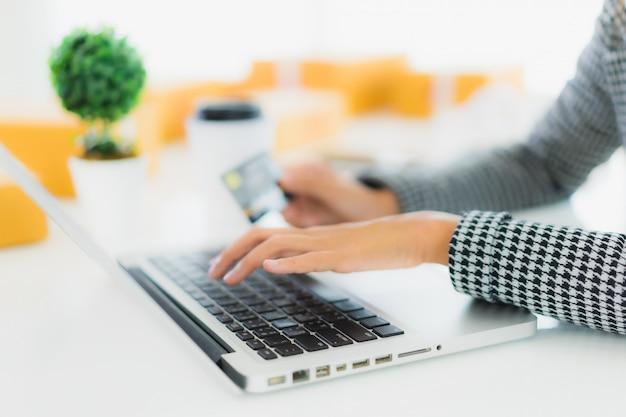 Bella giovane carta di credito asiatica di uso della donna del ritratto con il computer portatile per acquisto online