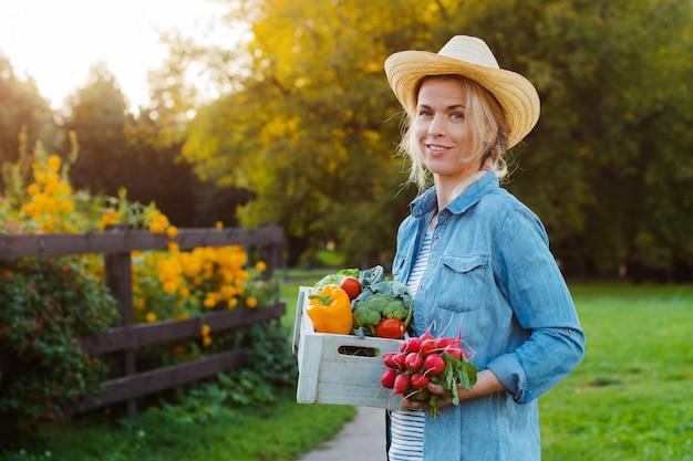 Bella giovane contadina di giovani anni in cappello con la scatola di verdure fresche ecologiche sul giardino