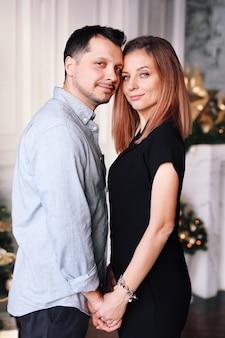 Bella giovane coppia a natale. una giovane donna e un uomo sorridono e si divertono insieme.