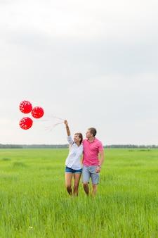 Bella giovane coppia abbracciare e baciare in un campo con palloncini colorati.