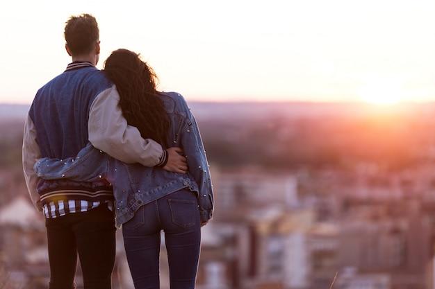 Bella giovane coppia in amore in piedi in un edificio sul tetto al tramonto.