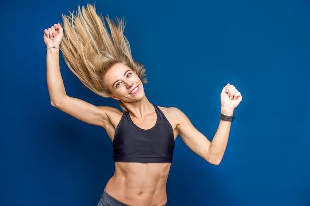 Bella giovane donna adatta sorridente in reggiseno sportivo con capelli fluenti. danza, palestra, concetto sottile