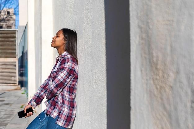 Bella giovane donna afroamericana che si appoggia su una parete bianca all'aperto nella via mentre tenendo un telefono e ascoltando musica