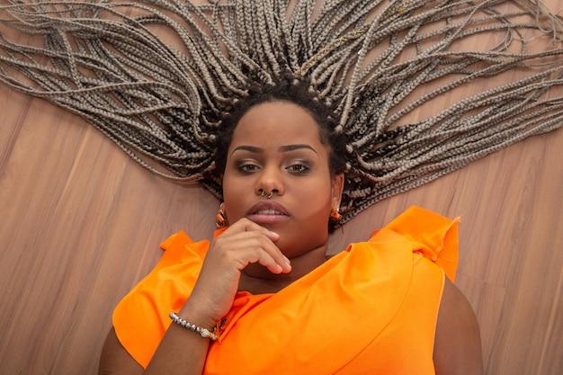 Bella giovane donna afroamericana con i capelli di terrore su legno