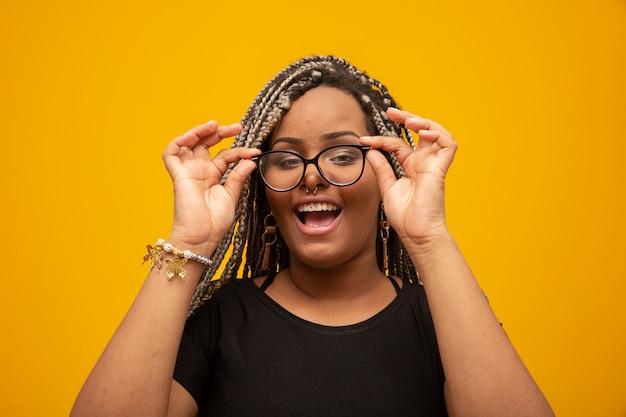 Bella giovane donna afroamericana con i capelli e gli occhiali di terrore su giallo