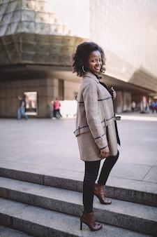 Bella giovane donna afroamericana con orecchini a cerchio afro e grandi in un cappotto alla moda, sorridente
