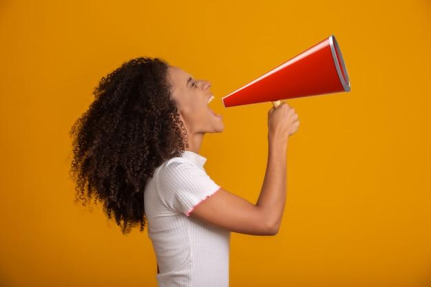 Bella giovane donna afroamericana sorridente con i capelli afro ricci che grida dal megafono sopra la parete gialla