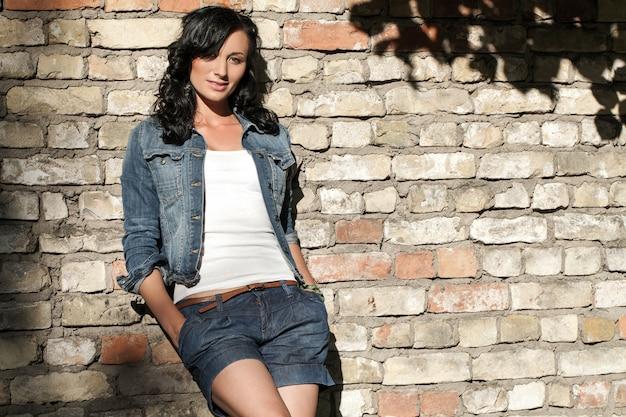 Bella giovane donna al muro di mattoni