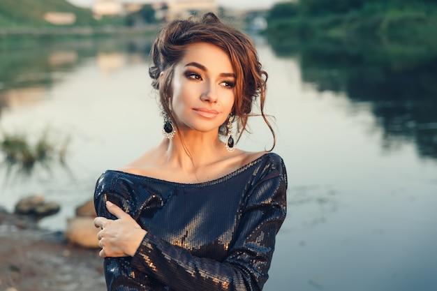 Bella giovane donna alla moda che propone in vestito al litorale del fiume