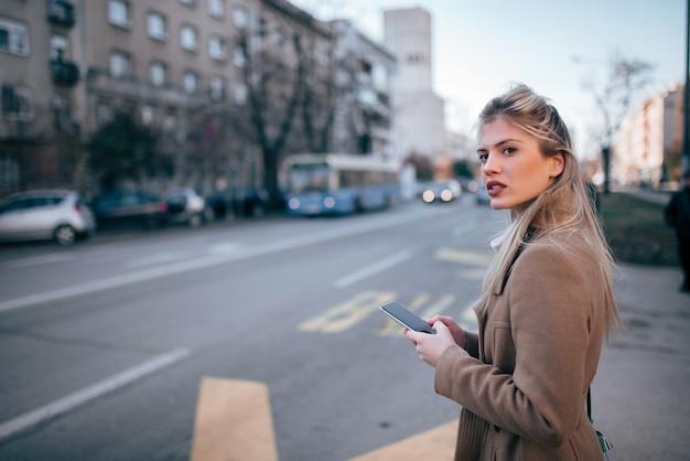 Bella giovane donna alla moda che utilizza smartpone mentre aspettando il taxi o il bus nella città.
