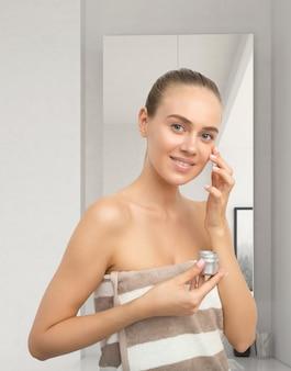 Bella giovane donna applicando crema per il viso
