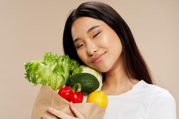 Bella giovane donna asiatica che abbraccia le verdure