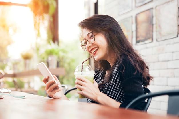 Bella giovane donna asiatica che beve tè verde fresco in bottiglia e che osserva sullo schermo del cellulare con il fronte di felicità