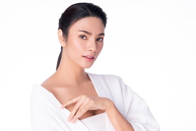Bella giovane donna asiatica che osserva mentre tocca la spalla che si sente così felice e allegra con pelle pulita e fresca sana, isolata su bianco, cosmetologia di bellezza,