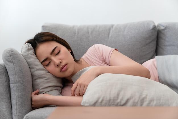 Bella giovane donna asiatica che si rilassa e che dorme sul sofà nel salone a casa